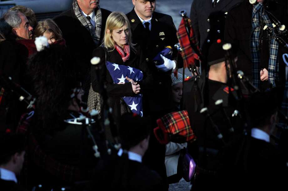 Kimberly Chiapperini, center, clutches the American flag presented to her during a funeral service for her husband Lt. Mike Chiapperini in Webster, N.Y., Sunday, Dec. 30, 2012. Chiapperini, 43, and fellow firefighter Tomasz Kaczowka, 19, were slain by gunman William Spengler in a fiery Christmas Eve ambush in a neighborhood on the shore of Lake Ontario. Two other firefighters remain hospitalized with bullet wounds. Photo: KEVIN RIVOLI, AP / FR60349 AP