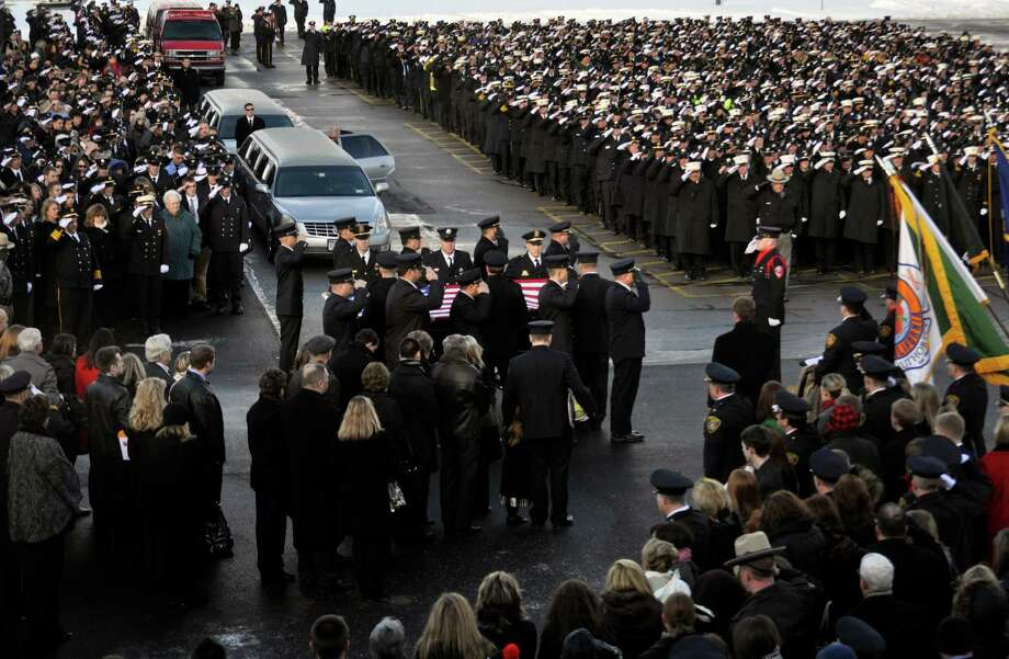Mourners hold a salute during the funeral service for Lt. Mike Chiapperini in Webster, N.Y., Sunday, Dec. 30, 2012. Chiapperini, 43, and fellow firefighter Tomasz Kaczowka, 19, were slain by gunman William Spengler in a fiery Christmas Eve ambush in a neighborhood on the shore of Lake Ontario. An estimated 5,000 first responders from across the state were in town for the weekend to attend calling hours for both men on Saturday at Webster Schroeder High School. Photo: KEVIN RIVOLI, AP / FR60349 AP