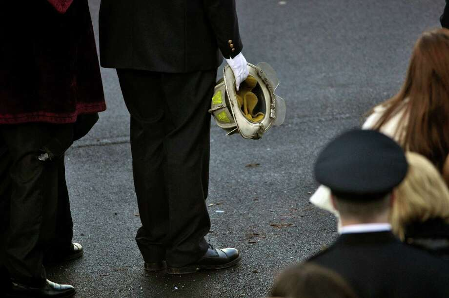 Nicholas Chiapperini holds his father's, Lt. Mike Chiapperini, helmet during a funeral service in Webster, N.Y., Sunday, Dec. 30, 2012. Lt. Mike Chiapperini, 43, and fellow firefighter Tomasz Kaczowka, 19, were slain by gunman William Spengler in a fiery Christmas Eve ambush in a neighborhood on the shore of Lake Ontario. Two other firefighters remain hospitalized with bullet wounds. Photo: KEVIN RIVOLI, AP / FR60349 AP