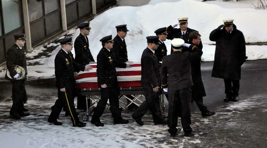 Pallbearers wheel Lt. Mike Chiapperini's flag covered casket to an awaiting fire truck during a funeral service in Webster, N.Y., Sunday, Dec. 30, 2012.  Chiapperini, 43, and fellow firefighter Tomasz Kaczowka, 19, were slain by gunman William Spengler in a fiery Christmas Eve ambush in a neighborhood on the shore of Lake Ontario. Two other firefighters remain hospitalized with bullet wounds. Photo: KEVIN RIVOLI, AP / FR60349 AP