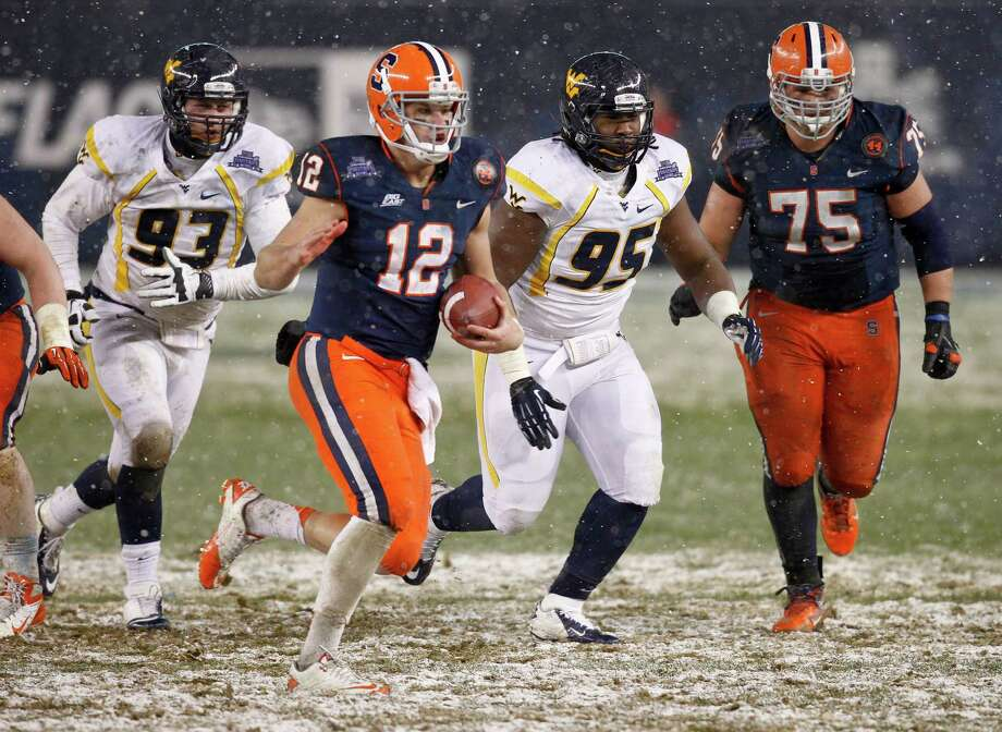 NEW YORK, NY - DECEMBER 29:  Ryan Nassib #12 of the Syracuse Orange scrambles in front of Christian Brown #95 of the West Virginia Mountaineers in the New Era Pinstripe Bowl at Yankee Stadium on December 29, 2012 in the Bronx borough of New York City. Photo: Jeff Zelevansky, Getty Images / 2012 Getty Images