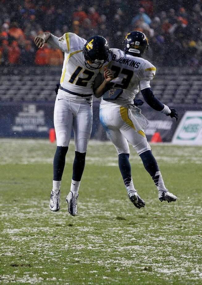 NEW YORK, NY - DECEMBER 29:  Geno Smith #12 and Brodrick Jenkins #23 of the West Virginia Mountaineers celebrate against the Syracuse Orange in the New Era Pinstripe Bowl at Yankee Stadium on December 29, 2012 in the Bronx borough of New York City. Photo: Jeff Zelevansky, Getty Images / 2012 Getty Images