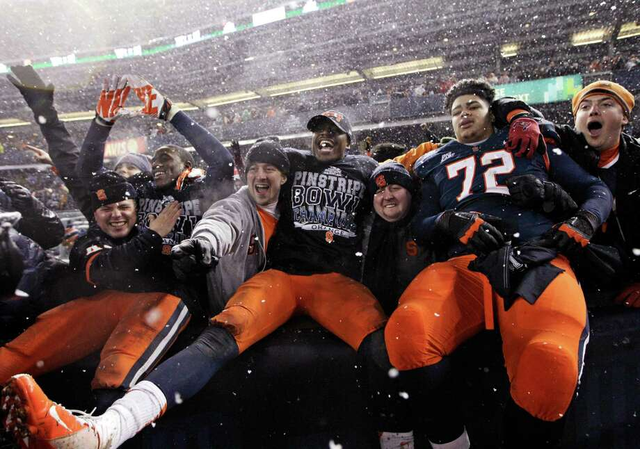 Syracuse players, including guard Ivan Foy (72), celebrate with fans after the team defeated West Virginia 38-14 in the Pinstripe Bowl NCAA college football game at Yankee Stadium in New York, Saturday, Dec. 29, 2012. Photo: Kathy Willens, AP / AP