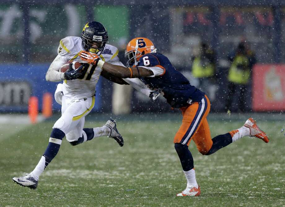 West Virginia wide receiver J.D. Woods (81) is stopped by Syracuse's Ritchy Desir (6) during the second half of the Pinstripe Bowl NCAA college football game at Yankee Stadium in New York, Saturday, Dec. 29, 2012. Syracuse won 38-14. Photo: Kathy Willens, AP / AP