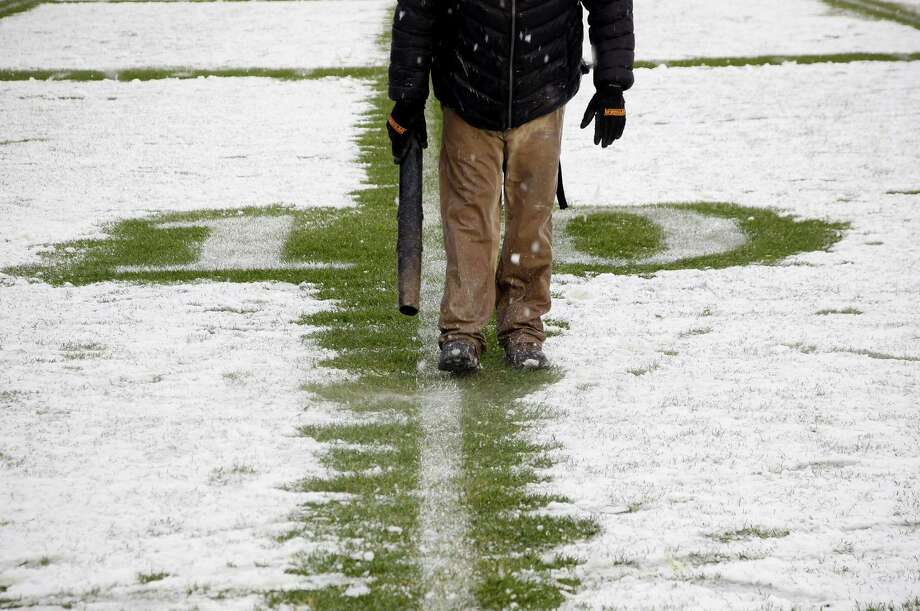 NEW YORK, NY - DECEMBER 29:  A member of the Yankee Stadium grounds crew clears snow from the 10-yard line before the New Era Pinstripe Bowl between West Virginia Mountaineers and the Syracuse Orange at Yankee Stadium on December 29, 2012 in the Bronx borough of New York City.  (Photo by Jeff Zelevansky/Getty Images)  BESTPIX Photo: Jeff Zelevansky, Getty Images / 2012 Getty Images