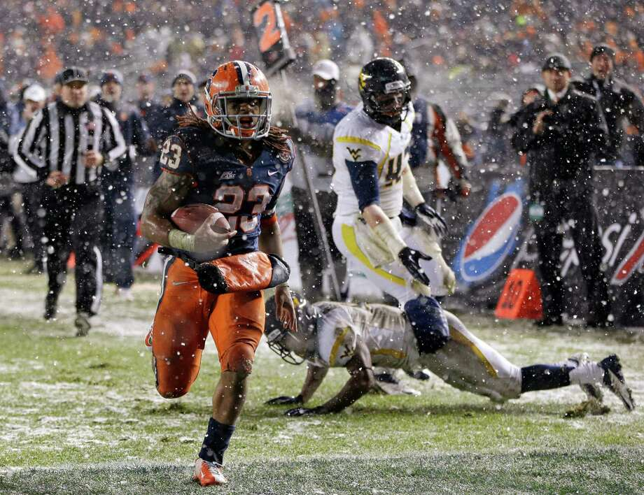 Syracuse running back Prince-Tyson Gulley (23) scores a touchdown, leaving West Virginia defenders in his wake during the third quarter of the Pinstripe Bowl NCAA college football game at Yankee Stadium in New York, Saturday, Dec. 29, 2012. Syracuse won 38-14. Photo: Kathy Willens, AP / AP
