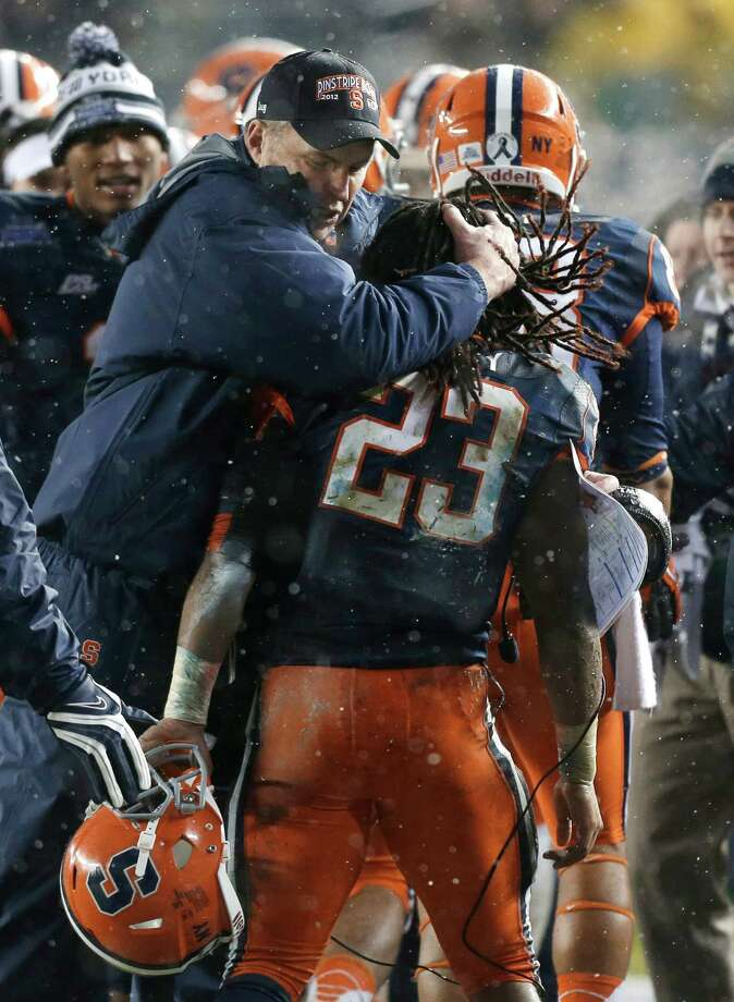 Syracuse coach Doug Marone embraces running back Prince-Tyson Gulley (23) who scored a second-quarter touchdown against West Virginia during the Pinstripe Bowl NCAA college football game at Yankee Stadium in New York, Saturday, Dec. 29, 2012. Photo: Kathy Willens, AP / AP