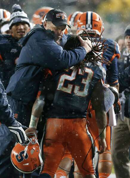Syracuse coach Doug Marone embraces running back Prince-Tyson Gulley (23) who scored a second-quarte