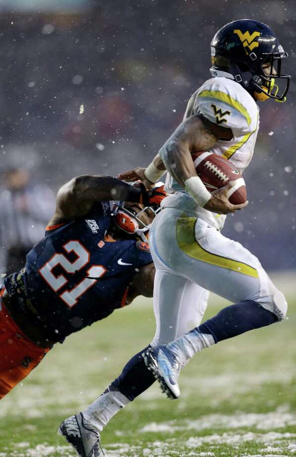 Syracuse safety Shamarko Thomas (21) tries to tackle West Virginia wide receiver Tavon Austin during the first half of the Pinstripe Bowl NCAA college football game at Yankee Stadium in New York, Saturday, Dec. 29, 2012. Photo: Kathy Willens, AP / AP
