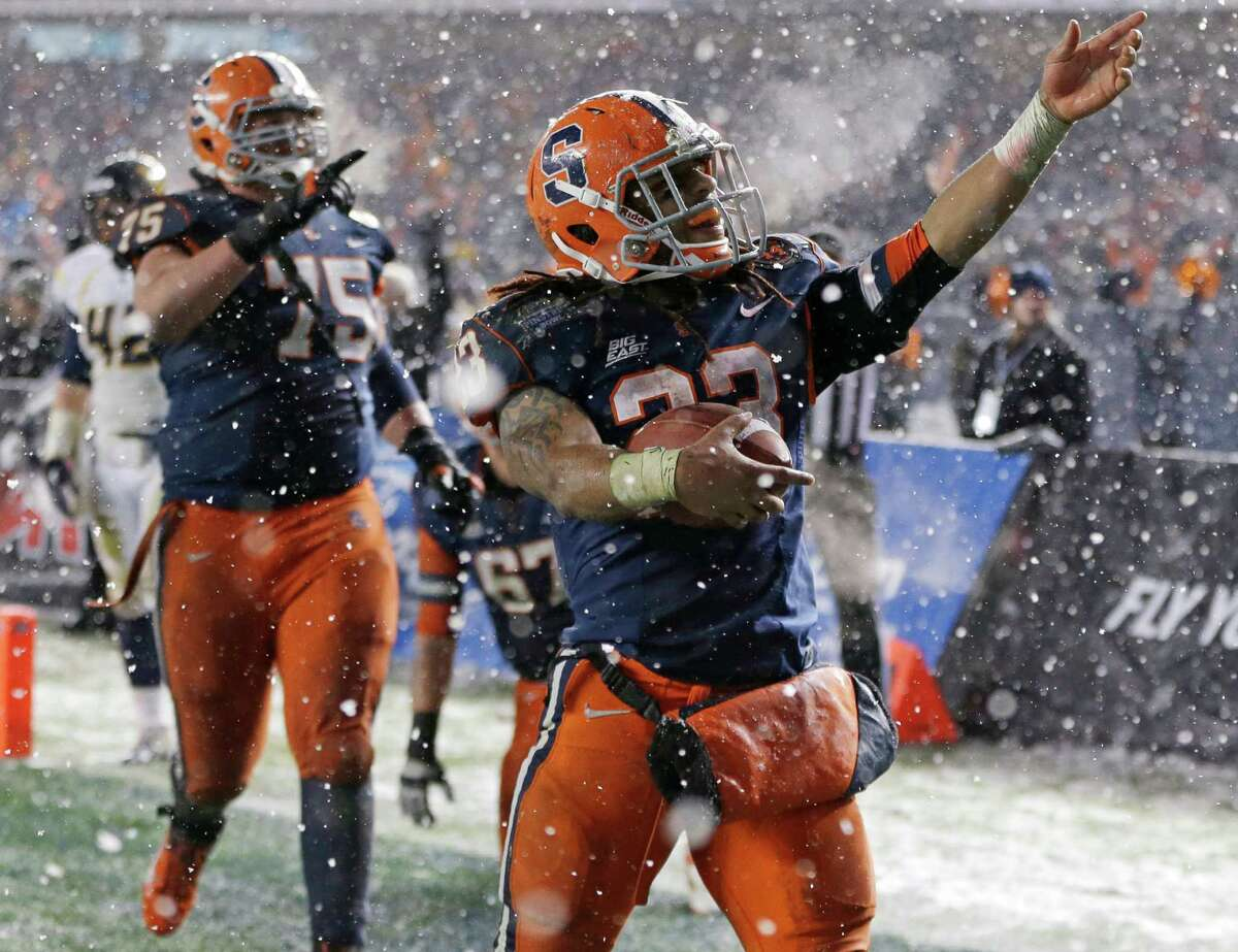Syracuse running back Prince-Tyson Gulley (23) and guard Zack Chibane (75) celebrate Gulley's third-quarter touchdown against West Virginia in the Pinstripe Bowl NCAA college football game at Yankee Stadium in New York, Saturday, Dec. 29, 2012. Syracuse won 38-14.