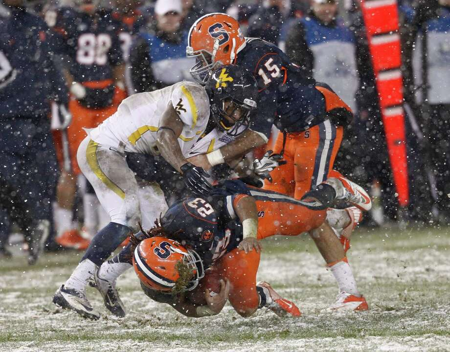 NEW YORK, NY - DECEMBER 29:  Prince-Tyson Gulley #23 of the Syracuse Orange is tackled by Curtis Smelley #41 of the West Virginia Mountaineers in the New Era Pinstripe Bowl at Yankee Stadium on December 29, 2012 in the Bronx borough of New York City. Photo: Jeff Zelevansky, Getty Images / 2012 Getty Images