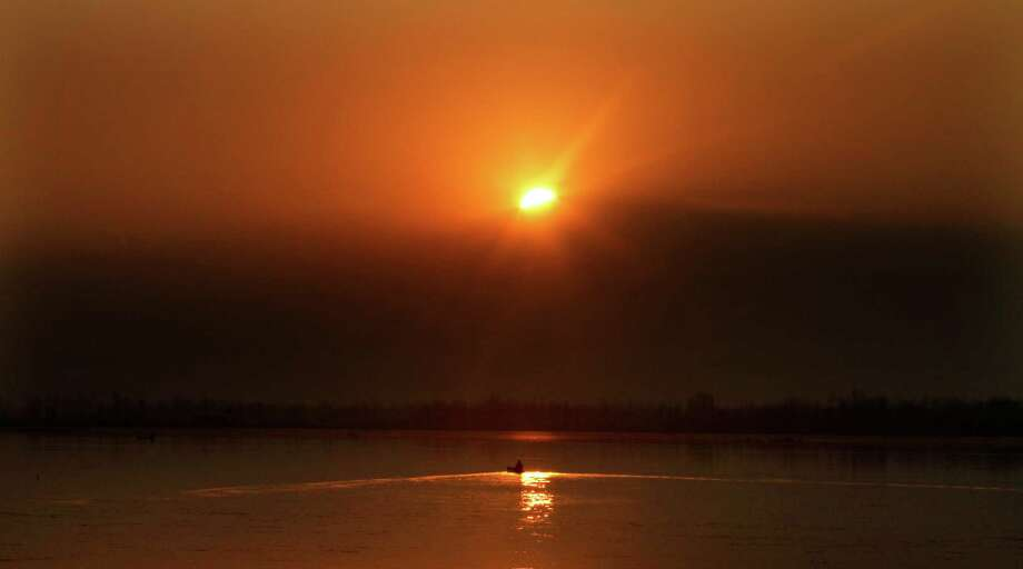 A Kashmiri boatman rows during the last sunset of the year 2012 at the Dal Lake in Srinagar, India. Photo: AP