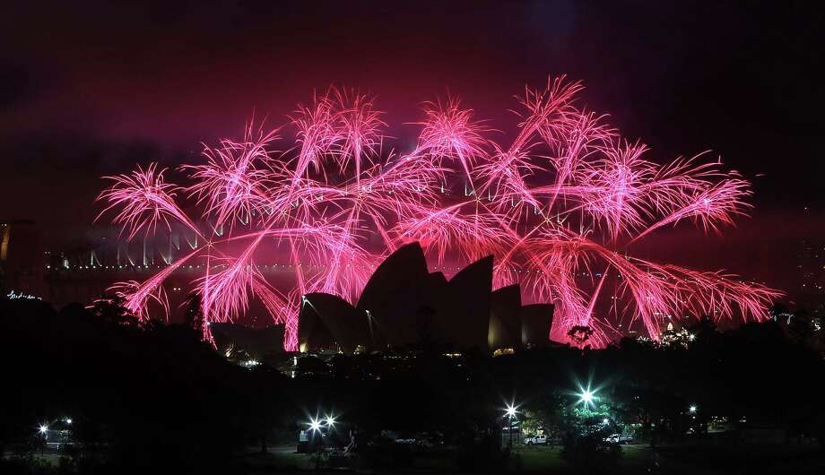 Fireworks explode behind the Opera House during the New Year celebrations in Sydney, Australia. Photo: AP