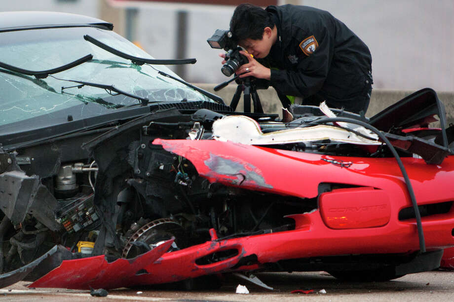 Officials investigate the scene of a fatal accident involving two vehicles in the Westbound lane of Highway 290, Monday, Dec. 31, 2012, in Houston. The driver of the red car was struck by a truck after the car collided with the median early Monday morning. The driver of the car was taken to a hospital where he was pronounced dead on arrival, meanwhile, the driver of the truck fled the scene. Photo: Cody Duty, Houston Chronicle / © 2012 Houston Chronicle