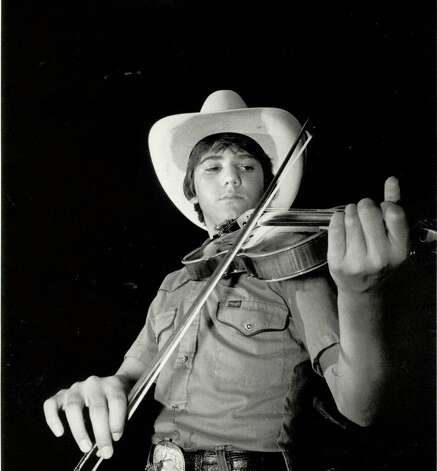 "Val Lindsey, a 14-year-old fiddler who doesn't like to sit while playing, practices his ""stroking"" in the night air. Photo: Enterprise Archives"