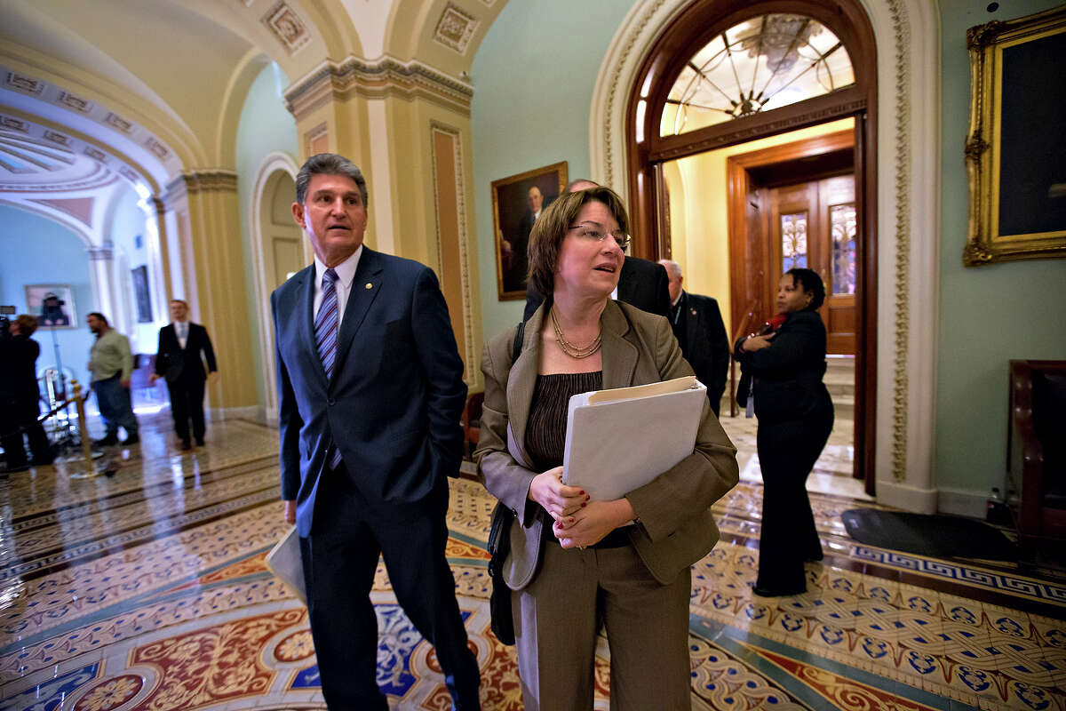 """Sen. Joe Manchin, D-W.V., left, Sen. Amy Klobuchar, D-Minn., right, leave the Senate chamber as the leadership negotiates a solution to the """"fiscal cliff."""" Klobuchar is trying to scale another cliff, running for Democratic presidential nomination."""