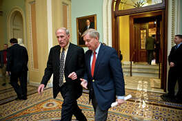 """Sen. Dan Coats, R-Ind., left, and Sen. Lindsey Graham, R-S.C., right, stride from the Senate chamber to a GOP caucus meeting as Congress convenes to negotiate a legislative path to avoid the so-called """"fiscal cliff"""" of automatic tax increases and deep spending cuts that could kick in Jan. 1., at the Capitol in Washington, Sunday, Dec. 30, 2012."""
