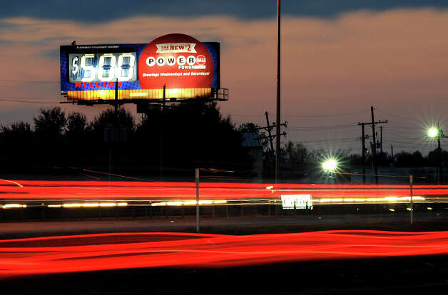 Cars travel Tuesday past a sign announcing today's $500 million Powerball game. Players have a 1 in 175 million chance in winning the jack pot.   Photo taken Tuesday, November 27, 2012 Guiseppe Barranco/The Enterprise Photo: Guiseppe Barranco, STAFF PHOTOGRAPHER / The Beaumont Enterprise