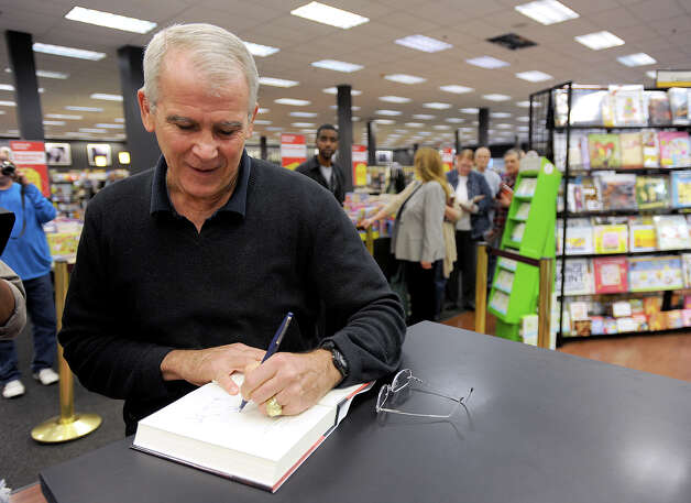 Oliver North's signs a copy of his new book at Books-A-Million in Beaumont Friday. The former Lieutenant Colonel describes his experiences in global situations and military action. Harry McKinley looks on. Photo taken Friday, November 29, 2012 Guiseppe Barranco/The Enterprise Photo: Guiseppe Barranco, STAFF PHOTOGRAPHER / The Beaumont Enterprise