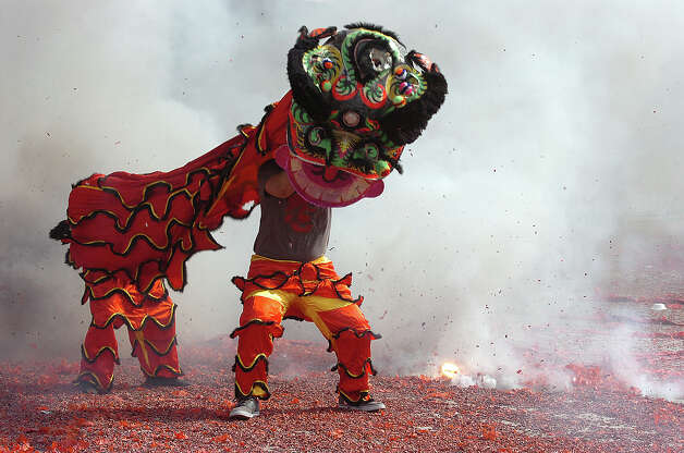 Surrounded by firecracker smoke, dragon dancers perform at several Vietnamese businesses on Port Arthur's 9th Avenue Monday. The nine-day celebration recognizes the ringing in of 2012 and the year of the dragon. Photo taken Monday, January 23, 2012 Guiseppe Barranco/The Enterprise Photo: Guiseppe Barranco, STAFF PHOTOGRAPHER / The Beaumont Enterprise