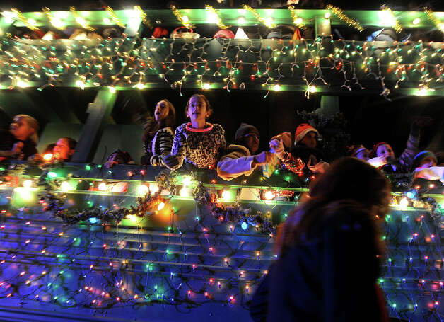 Children toss candy and trinkets at the Nederland Lighted Christmas Parade on Tuesday. Waiting crowds watched as several floats lit up Nederland Avenue.  Photo taken Tuesday, December 11, 2012 Guiseppe Barranco/The Enterprise Photo: Guiseppe Barranco, STAFF PHOTOGRAPHER / The Beaumont Enterprise