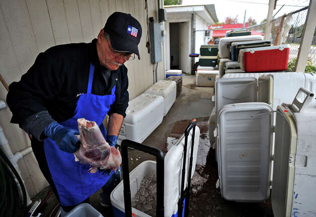 Joey Ancelet sifts through one of several coolers stacked behind his family's deer processing shop in Port Arthur on Friday. Ancelet's son, Ryan Ancelet said the company's recent growth is preventing a decrease in business regardless of this year's slow deer season.  Photo taken Friday, November 30, 2012 Guiseppe Barranco/The Enterprise Photo: Guiseppe Barranco, STAFF PHOTOGRAPHER / The Beaumont Enterprise