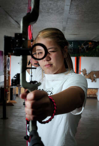"Marlee LeBlanc, 13, demonstrates her stance with her compound bow at Precision Archery in Bridge City. A fan of the movie ""The Hunger Games,"" Lundy said she wants to learn to use the bow to hunt. Photo taken Friday, July 20, 2012 Guiseppe Barranco/The Enterprise Photo: Guiseppe Barranco, STAFF PHOTOGRAPHER / The Beaumont Enterprise"