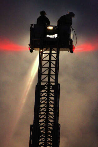 San Antonio firefighters on a ladder platform spray water on houses on the 400 block of West Lubbock early Monday morning December 31, 2012. San Antonio fire captain David Tedford said two houses were involved upon the fire department's arrival and another house was exposed to the threat of the fire. Tedford said there were no injuries during the fire and that arson was investigating the cause of the fire. Photo: JOHN DAVENPORT, San Antonio Express-News / ©San Antonio Express-News/Photo Can Be Sold to the Public