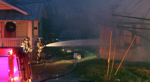 San Antonio firefighters spray water on a house on the 400 block of West Lubbock early Monday morning December 31, 2012. San Antonio fire captain David Tedford said two houses were involved upon the fire department's arrival and another house was exposed to the threat of the fire. Tedford said there were no injuries during the fire and that arson was investigating the cause of the fire. Photo: JOHN DAVENPORT, San Antonio Express-News / ©San Antonio Express-News/Photo Can Be Sold to the Public