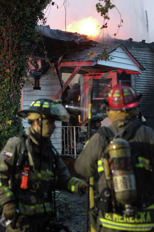 San Antonio firefighters work at the scene of a two alarm fire on the 400 block of West Lubbock early Monday morning December 31, 2012. San Antonio fire captain David Tedford said two houses were involved upon the fire department's arrival and another house was exposed to the threat of the fire. Tedford said there were no injuries during the fire and that arson was investigating the cause of the fire. Photo: JOHN DAVENPORT, San Antonio Express-News / ©San Antonio Express-News/Photo Can Be Sold to the Public