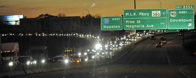 Traffic at 6 p.m. Monday evening can be seen from the east bound side of the bridge trying to enter the westbound flow over the bridge from downtown. Contract workers with the Texas Department of Transportation this week are constructing new footings for the $58 million Neches River/Purple Heart Memorial Bridge replacement project. Eastbound bridge traffic was expected to be moved into westbound lanes of Interstate 10 later this month. Marc Shepherd, department spokesman, said Monday that the lane switch will probably not happen until early next year. According to Shepherd, crews are still awaiting contractors to begin the process of removing the eastbound lanes of the bridge. Until those contractors are in place, drivers will continue to use both sides of the bridge. Construction on the bridge, which serves 80,000 drivers a day, is expected to continue into the fall of 2015. The nearly 60-year-old bridge is being replaced because of an increasing number of potholes that transportation experts said would become a bigger problem in the future.Photo taken Monday, November 12, 2012 Dave Ryan/The Enterprise