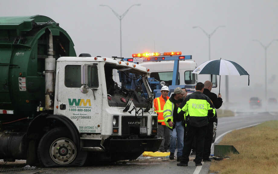 Police and wrecker crews work at the scene of a fatal accident involving a garbage truck that took place about 5:30 a.m. on Loop 410 near West Military drive. The driver of the truck was ejected from the vehicle. No other vehicles were involved. Photo: JOHN DAVENPORT, San Antonio Express-News / ©San Antonio Express-News/Photo Can Be Sold to the Public