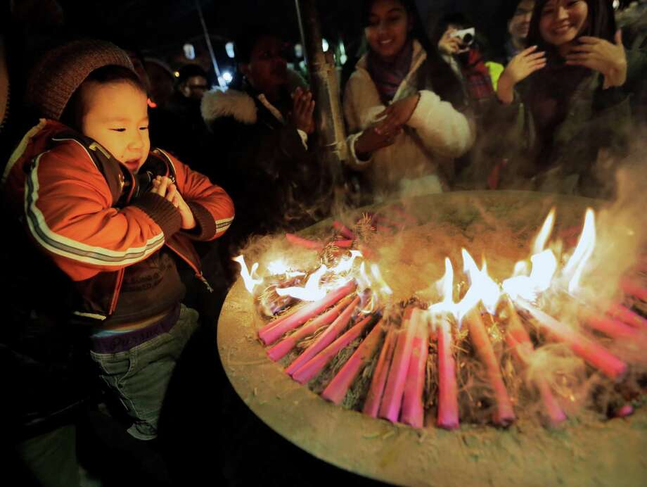 A boy prays around a fire believed to invoke divine help during his first visit of the year to the Zojoji Buddhist temple in Tokyo. Photo: AP