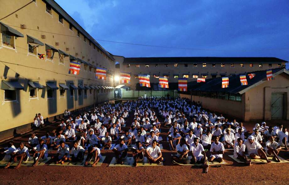 Sri Lankan inmates of the Welikada prison pray during a religious ceremony on the eve of new year.  Inmates of the Welikada prison, one of the largest prisons in Sri Lanka, housing over 4,000 prisoners, invoked blessings and ushered in the new year by engaging in Buddhist rituals. Photo: Eranga Jayawardena