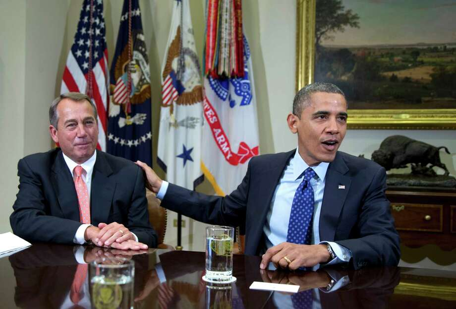 In this Nov. 16, 2012 file photo, President Barack Obama acknowledges House Speaker John Boehner of Ohio while speaking to reporters in the Roosevelt Room of the White House in Washington. A dreaded package of tax increases and deep spending cuts to domestic and defense programs loomed over the economy in 2012 as Congress and the White House negotiated the budgetary steps needed to avoid it. (AP Photo/Carolyn Kaster, File) Photo: Carolyn Kaster, Associated Press / AP