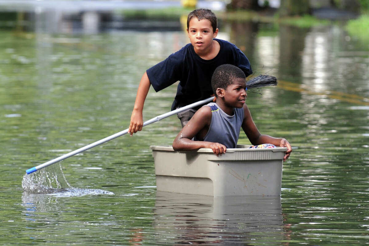 Iranistan Aveune, Bridgeport Nicolas Daniels, 9 (seated), and Joaquin Ortiz, 10, try to navigate the flood waters on Iranistan Ave., in Bridgeport, Conn. following Friday's storm, Aug. 10th, 2012.