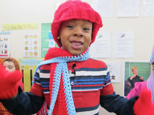 A child in the NEON Child Development Program shows off the gifts received from RSVP recently. Photo: Contributed Photo