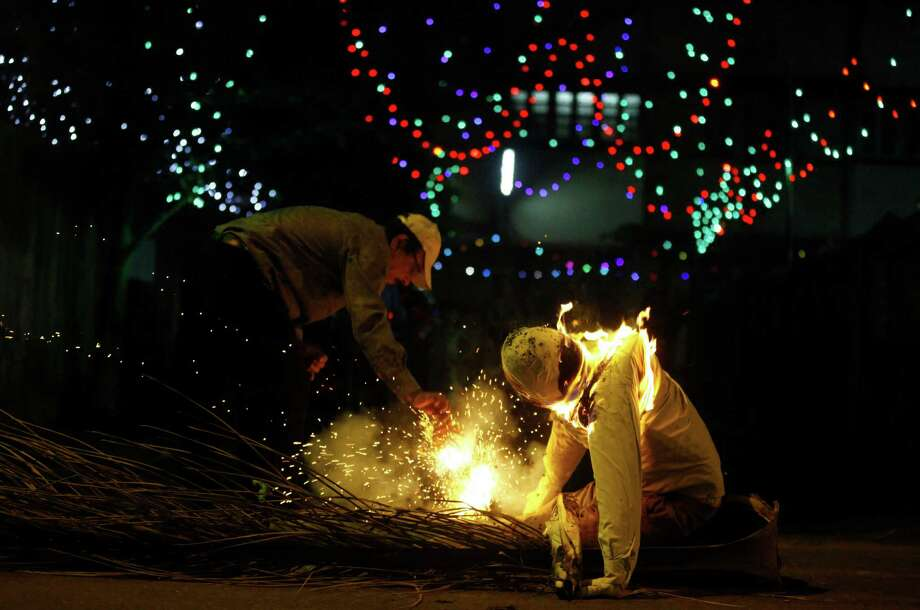 A man lights an Old Man effigy which symbolizes burning the past and getting ready to start a happy New Year without bad memories of the past in Mumbai, India, Tuesday, Jan. 1, 2013.(AP Photo/Rafiq Maqbool) Photo: Rafiq Maqbool, Associated Press / AP