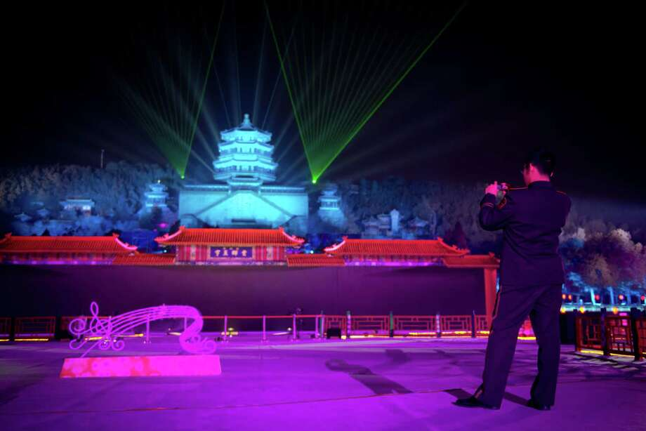 A paramilitary soldier takes a photo as a light show illuminates the Summer Palace prior to a new year count-down event in Beijing on December 31, 2012. AFP PHOTO / Ed JonesEd Jones/AFP/Getty Images Photo: ED JONES, AFP/Getty Images / AFP