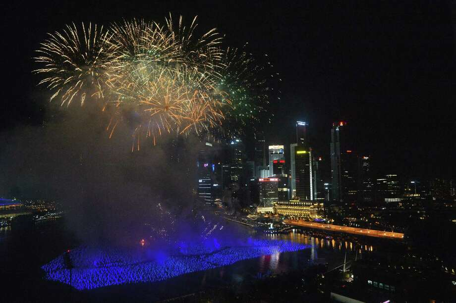 Fireworks illuminate the sky to usher the new year at the Marina Bay in Singapore on January 1, 2013. The spectacular fireworks burst across the skyline as ten of thousand people watch the eight-minute display.  AFP PHOTO/ROSLAN RAHMANROSLAN RAHMAN/AFP/Getty Images Photo: ROSLAN RAHMAN, AFP/Getty Images / AFP