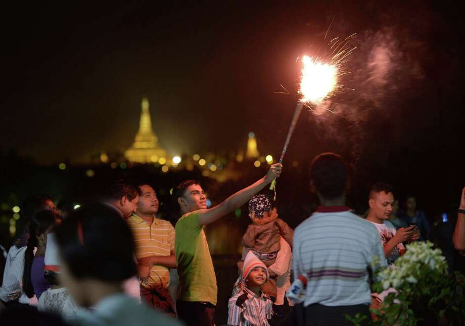 People wait before the countdown to the New Year near the Shwe Da Gon pagoda and Kandawgyi Lake in Yangon on December 31, 2012. Some 50,000 people were expected to gather at the revered golden Shwedagon Pagoda in Yangon for the city's first public countdown to the New Year and fireworks. AFP PHOTO / Ye Aung ThuYe Aung Thu/AFP/Getty Images Photo: YE AUNG THU, AFP/Getty Images / YE AUNG THU