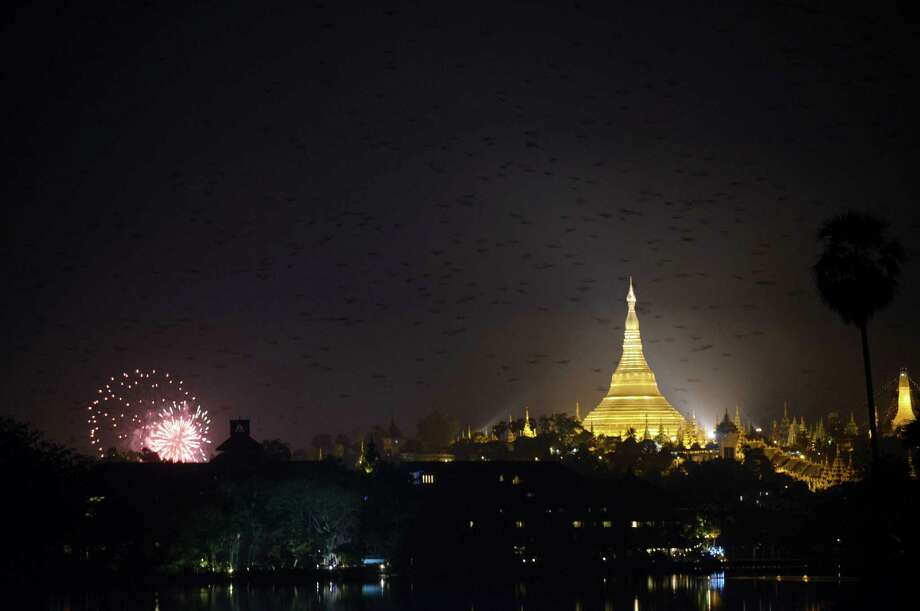 A view of birds scattering as New Year;s fireworks go off near the Shwe Da Gon pagoda at Kandawgyi Lake in Yangon on December 31, 2012. Some 50,000 people were expected to gather at the revered golden Shwedagon Pagoda in Yangon for the city's first public countdown to the New Year and fireworks. AFP PHOTO / Ye Aung ThuYe Aung Thu/AFP/Getty Images Photo: YE AUNG THU, AFP/Getty Images / AFP