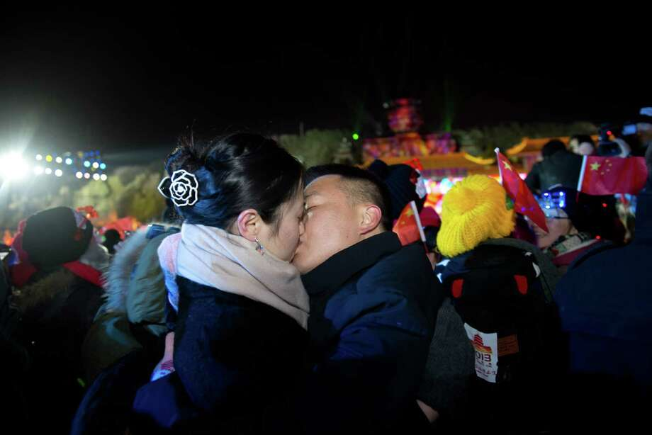 Two revellers kiss each other as they celebrate the new year during a count-down event at the Summer Palace in Beijing on January 1, 2013. AFP PHOTO / Ed JonesEd Jones/AFP/Getty Images Photo: ED JONES, AFP/Getty Images / AFP