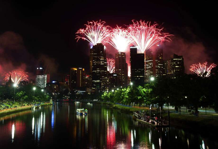 People watch the New Year's Eve fireworks as part of New Year's Eve celebrations at the riverside of Yarra River in Melbourne, Australia, Monday, December 31, 2012. (Bai Xue/Xinhua/Zuma Press/MCT) Photo: Bai Xue, McClatchy-Tribune News Service / Zuma Press
