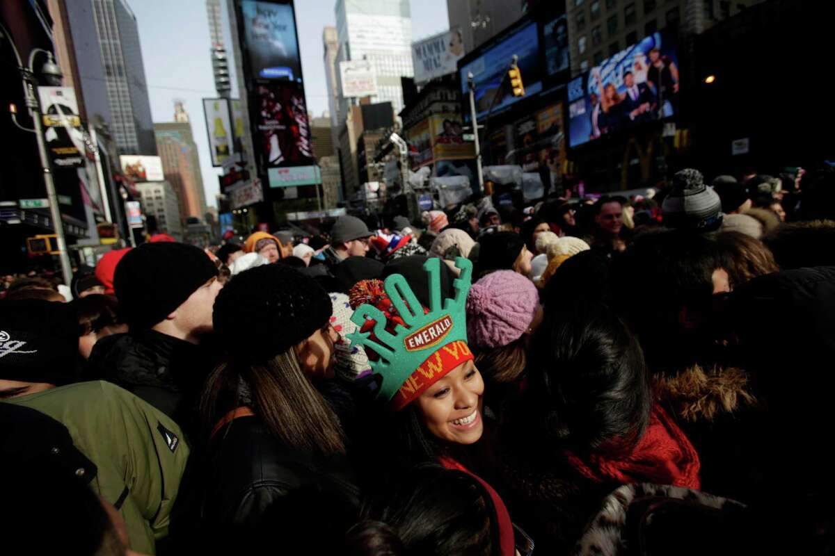 Jackielyn Junio, center, from Silver Springs, Md., waits to be searched and claim a spot in Times Square in New York, Monday, Dec. 31, 2012. One million people are expected to cram into the area for the countdown.
