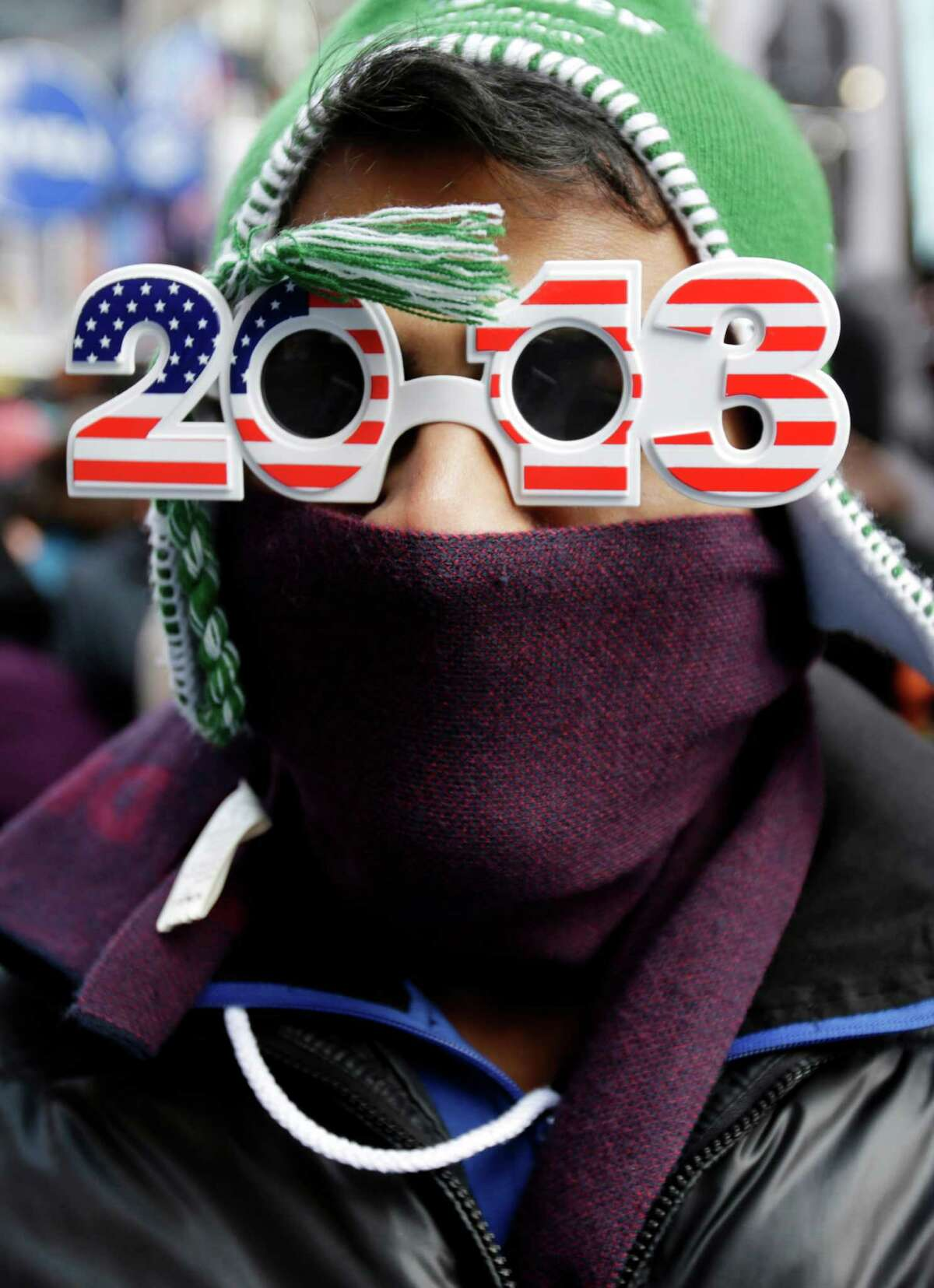 Pranav Patel of Toronto, is bundled up as he waits Monday morning, Dec. 31, 2012 for midnight in Times Square in New York, Monday, Dec. 31, 2012. An estimated 1 million people were expected to cram into district to see the crystal ball drop and countdown to 2013, organizers said.