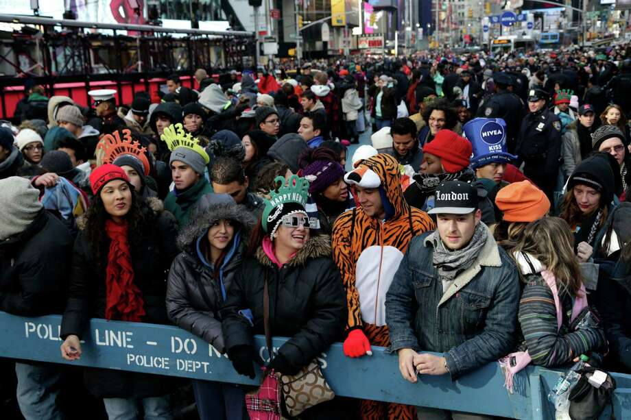 People who arrived Monday morning Dec. 31, 2012, line a front row spot to watch the ball drop in Times Square in New York.  An estimated 1 million people were expected to cram into district to see the crystal ball drop and countdown to 2013, organizers said. Photo: Seth Wenig, AP / AP