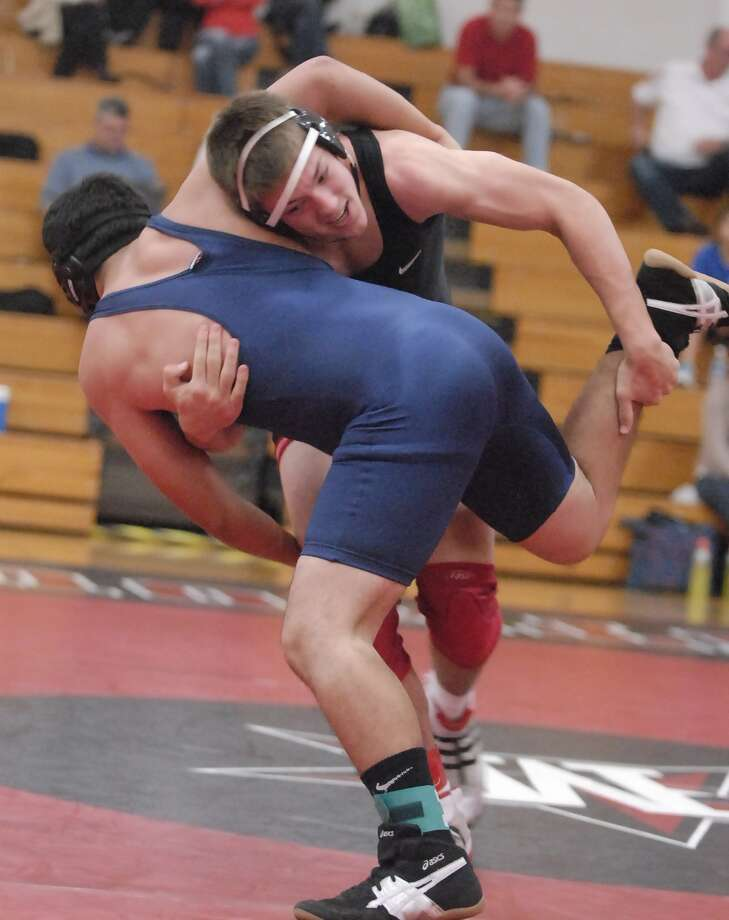 Sergio Castillo with Lamar Consolidated (blue) and Nathan Avery with St. John's (black with red knee pads) during their wrestling tournament at St. John's Saturday 12/03/11. Photo by Tony Bullard. Photo: Tony Bullard / Credit: for the Chronicle