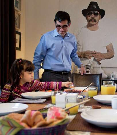 Dr. Mike Flores, right, sits down for breakfast with his daughter, Mara Flores, Sunday, Dec. 16, 2012, at his home in San Antonio. Photo: Darren Abate, Darren Abate/For The Express-New