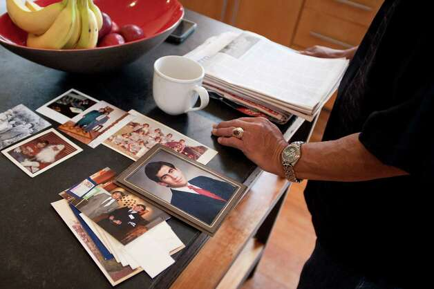 Ruben Flores reads a newspaper next to an assortment of family photos featuring himself and his son, Dr. Mike Flores, Sunday, Dec. 16, 2012, in San Antonio. Photo: Darren Abate, Darren Abate/For The Express-New